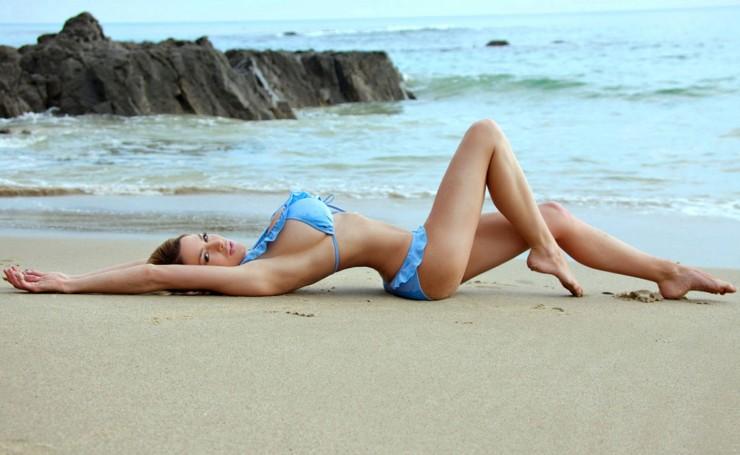 Картинка девушка лежит на пляже боком на шезлонге